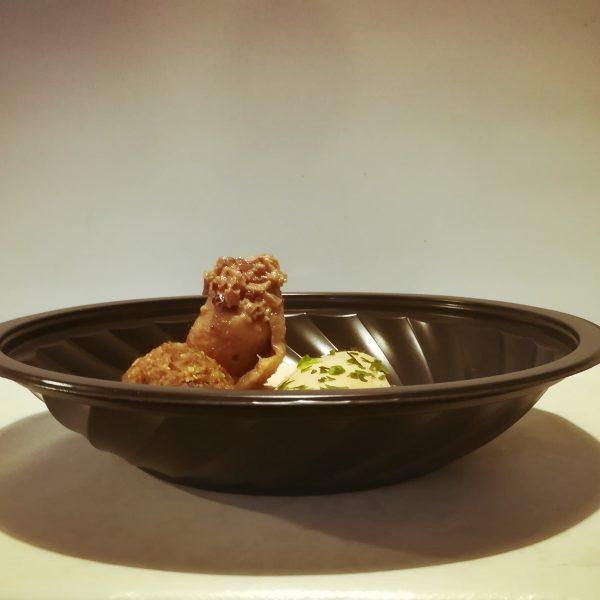 Piatto per microonde nero con carne mista su crema al latte e cipolle rosse carmellate