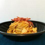 Piatto per consegne con linguine alla carbonara in cialda di parmigiano